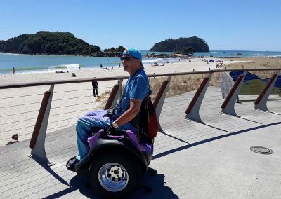 A woman on a purple Omeo at a beach lookout. The sand is white. There are two islands off the edge of the beach. It's a hot sunny day and the beach is scattered with people.
