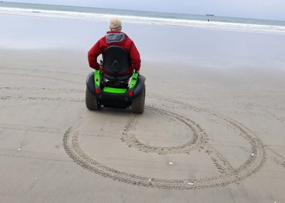 Man in red jacket on a green Omeo doing figure 8's on the wet sand at the beach.