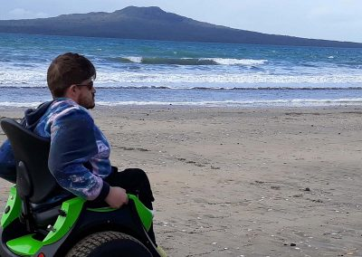 Man on green Omeo riding along the beach. Ocean and volcanic island in the background.