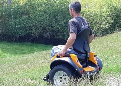 Man riding an Omeo down a steep incline in long grass