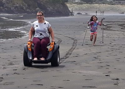 Lady on orange Omeo riding along on beach. Young girl running behind, clutching the ladies crutches.