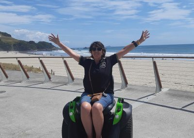 Woman on an Omeo at the beach with her arms raised, the sky is blue and the sand is white