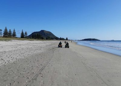 Two people are riding Omeos on a long stretch on beach. Mt Maunganui is in the distance.