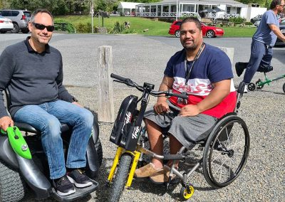 A man sitting on an Omeo and another man is in a wheelchair with a powered trike attachment