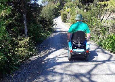 Person riding an Omeo along a gravel walking trail in the New Zealand bush