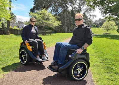 Two people riding Omeos on a gravel track in a park