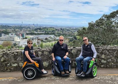 3 people on Omeos at the top of a mountain with views to Auckland