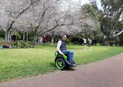 Man riding an Omeo on the grass in a park filled with cherry trees in blossom. People in the background are taking pictures of the trees