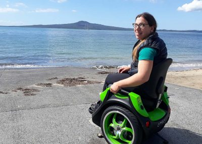 Lady on an Omeo, at the edge of a beach. A volcanic island in the distance.