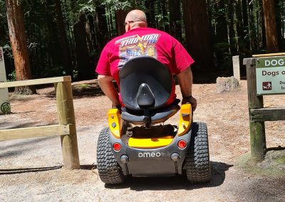 Man on an orange Omeo heading into a redwood forest
