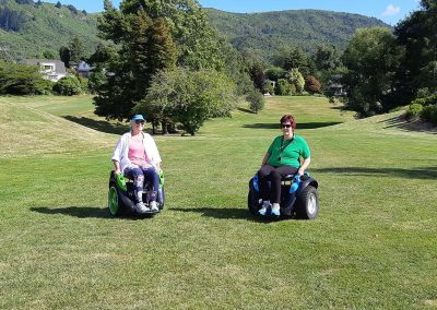 Two people riding Omeos on a golf course