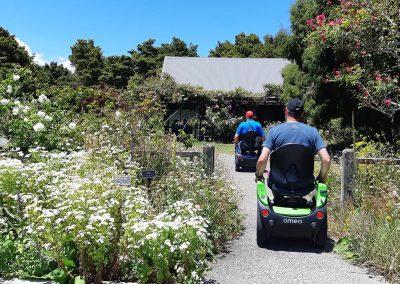 Two people riding Omeos through a garden