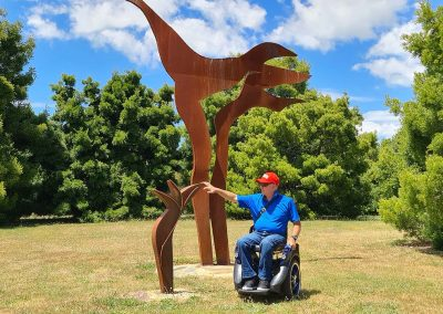 Man in bright blue shirt, seated on an Omeo, next to a sculpture in park. The sky is also bright blue with fluffy white clouds.