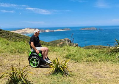Man seated on Omeo with beautiful ocean view. Sand hills, rocks and blue sparkling sea behind him.