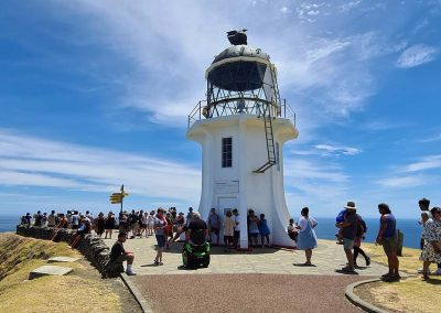 Picture of the lighthouse at the top of New Zealand. It is surround by people, including a man on an Omeo. The sky is deep blue with an unusual cloud formation surrounding the lighthouse.