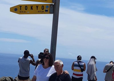 Man on Omeo and lady standing beside him, in front of sign post at the top of New Zealand
