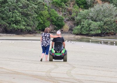 A women walking along beside a man seated on an Omeo. They are on a beach. The women has her arm around his shoulders.