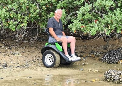 A man seated on an Omeo on the sea shore. The tyres are covered with wet sand.