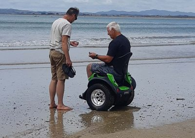 Man on an Omeo and another man inspecting shells on the shore of a beach.