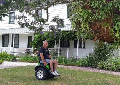 Man seated on a green Omeo, under a beautiful tree in the yard. A beautifully kept historical house painted white, behind him.