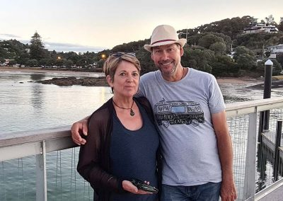 Lady and Man on a wharf just before sun down. Water, hills and street lights along the beach, in the distance.