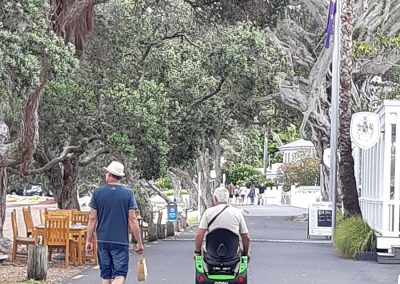 Man walking beside another man on an Omeo on a tree lined road