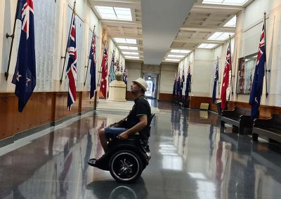 Man on a black Omeo inside a War Museum. He is staring at a list of fallen soldiers. There is a line of flags down one side of a gallery. The floors are highly polished.