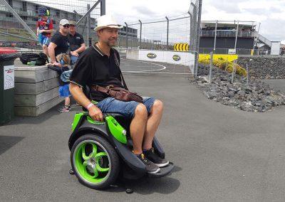 Man riding an Omeo at a car racing track