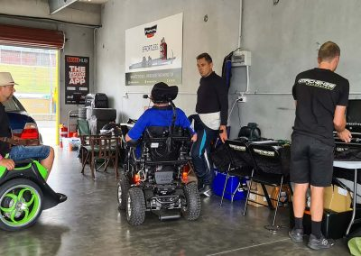 Inside a racetrack pit garage. Two team mates, one racing care, one man on an Omeo and another man in a motorised wheelchair.