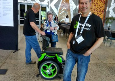 Two men and a lady with a green Omeo, inside an event centre.