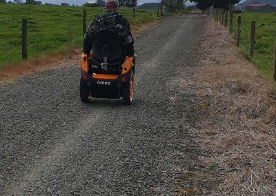Man on orange Omeo riding along a long gravel bike trail.